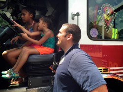 Orange County Firefighters showing students the inside of a fire truck.