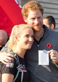 Prince Harry hugs Afghanistan veteran Kirstie Ennis, 24, as he welcomes six ex-servicemen and women who have travelled the length and breadth of Britain over 72 days since starting the arduous journey in Moray, Scotland, in August, as part of Walking With The Wounded (WWTW) Walk of Britain, as they reach the finishing line at Buckingham Palace in central London.